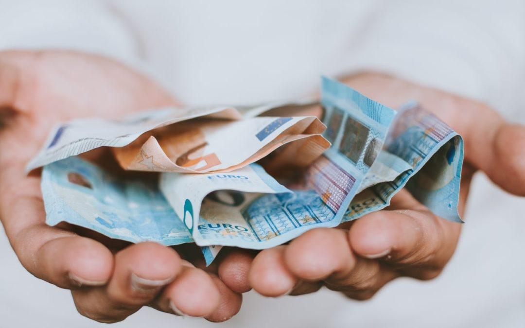 Hand mit Geldscheinen (Bild: Christian Dubovan on Unsplash)