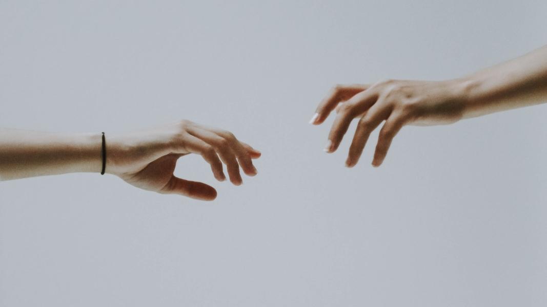 Two hands about to hold (Bild: fotografierende auf Unsplash)