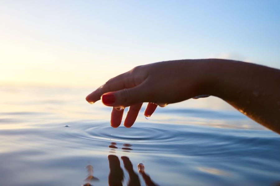 Person about to touch water (Bild: Yoann Boyer auf Unsplash)
